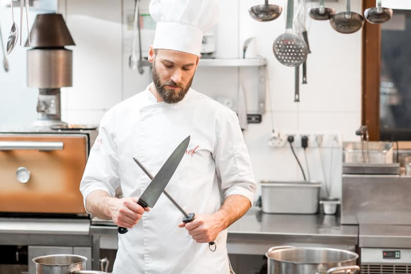 A chef sharpening a knife, highlighting the need to have a good sharpener. To help, this article has the best knife sharpener review Australia, including electric knife sharpener reviews Australia.